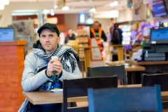 Man drinking coffee sitting in Cafe. Focus is on face. Shallow depth of field.
